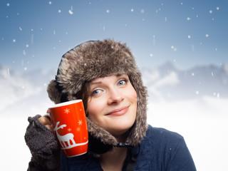 Frau trinkt Glühwein in Winterlandschaft