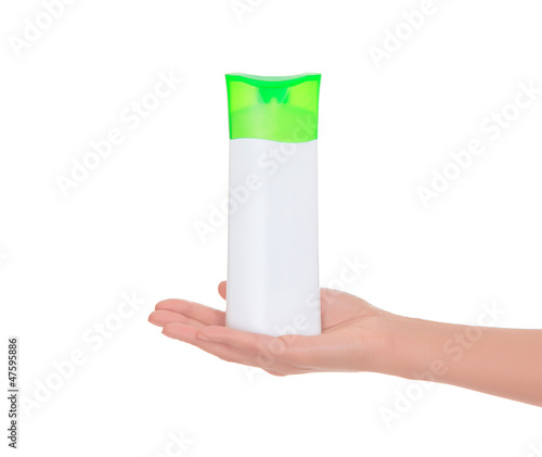 Bottle of a shampoo on female hand
