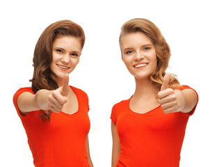 wo teenage girls in red t-shirts showing thumbs up