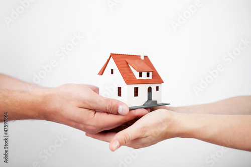 Couple holding miniature house