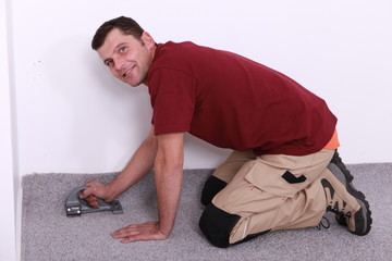 man on all fours stapling carpet