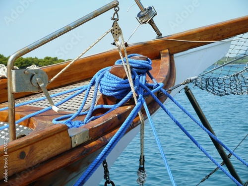 A blue rope on a belaying cleat of a wooden ship