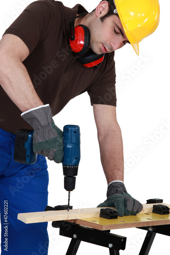 Workman drilling a hole into a wooden plank