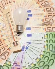 Glühbirne und Thermometer mit Geldscheinen