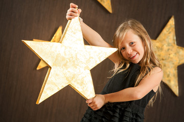 Cute girl holding big golden star.