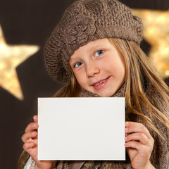 Cute girl with beanie holding white card.