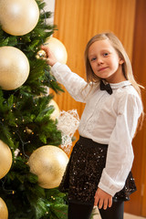Little girl decorating christmas tree.