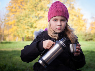 little beautiful blond girl pours tea from a thermos