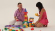 Two adults playing with toy blocks and trying to build a castle