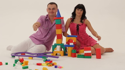Two grown-ups sitting next to a toy castle