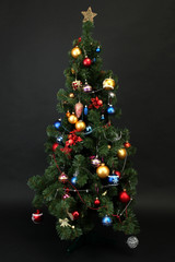 Decorated Christmas tree isolated on black