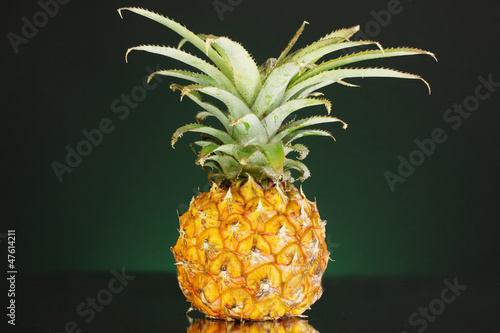Ripe pineapple on dark green background