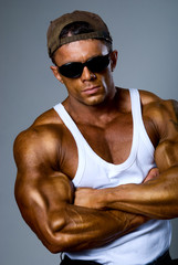 Handsome muscular man on gray background