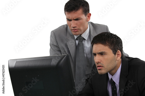 Two serious businessman concentrating on laptop screen
