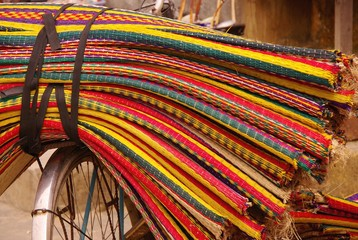 Colorful straw mats on the lugage carrier of a bicycle