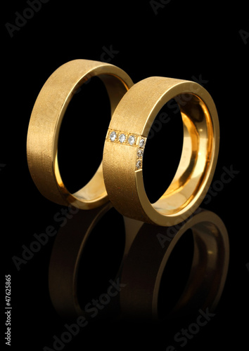 gold wedding rings with diamonds isolated on black