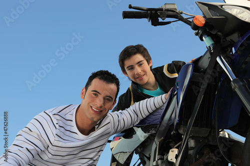 man and teenager watching motorbike