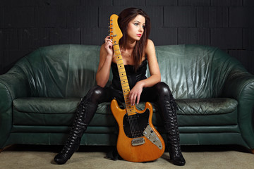 Sexy guitar player sitting on couch