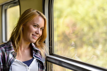 Happy woman looking out train window pensive