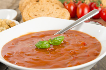 Chunky tomato and red pepper soup with basil and bread slices.