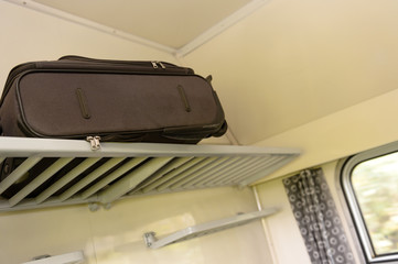 Baggage sitting on train rack in compartment