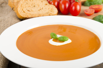 Cream of tomato soup with crème fraîche, bread & basil leaves