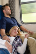 Couple resting with eyes closed in train