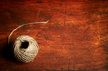 Skein of jute twine on the wooden background
