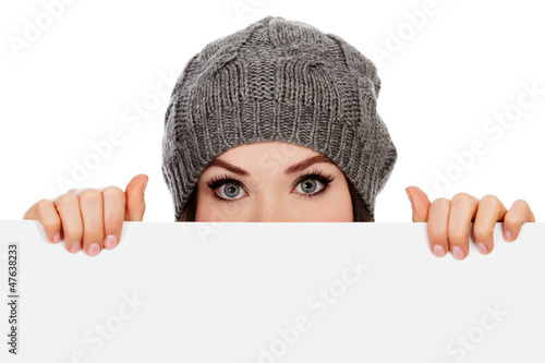 Girl in knitted hat looking over white board, white background