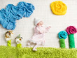 Newborn baby lying on creative nature background folded from tow