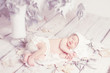 Newborn baby sleeping on leaves over white wooden background. Fi