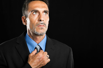 Businessman adjusting his look on a dark background