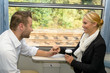 Woman and man on train holding hands