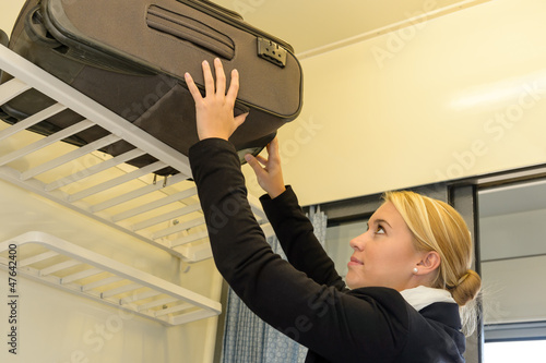 Woman putting her luggage on train rack