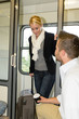 Man sitting train compartment woman getting in