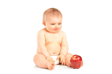 Baby boy sitting and looking at an apple