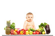 Baby sitting on a table full of different fruits and vegetables