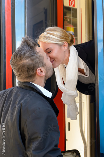 Man kissing woman goodbye train leaving romance