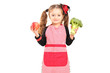 A smiling girl with apron holding a broccoli and red apple