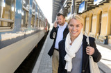 Woman smiling in train station man phone