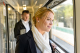 Woman in train looking pensive on window