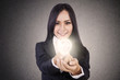 Businesswoman give lit lightbulb
