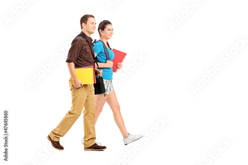 Full length portrait of a two students holding books and walking