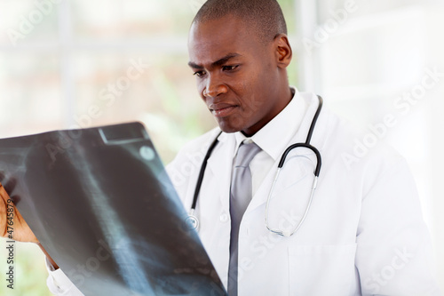 african american doctor looking at patient's x-ray in office