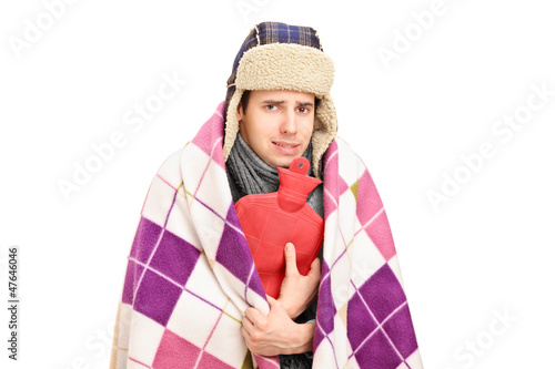 Sick man covered with blanket holding a hot-water bottle