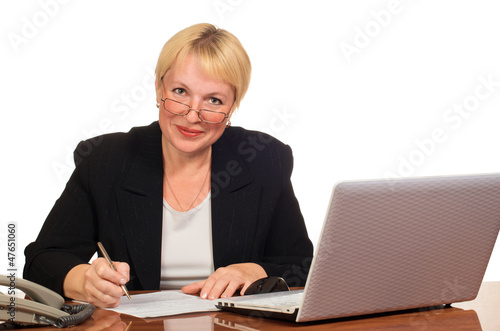 Mature businesswoman writes and looks at you with smile