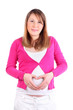 Pregnant woman wearing in pink blouse depicts heart on belly