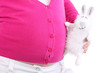 Toy rabbit with unreal design touches belly of pregnant woman