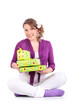 Pregnant woman sits on floor and holds boxes with gifts isolated