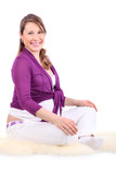 Smiling pregnant woman sits on white fur and looks at camera